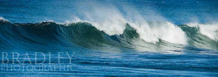 A straight shot of a wave coming in at Carmel beach in California.  The wind
