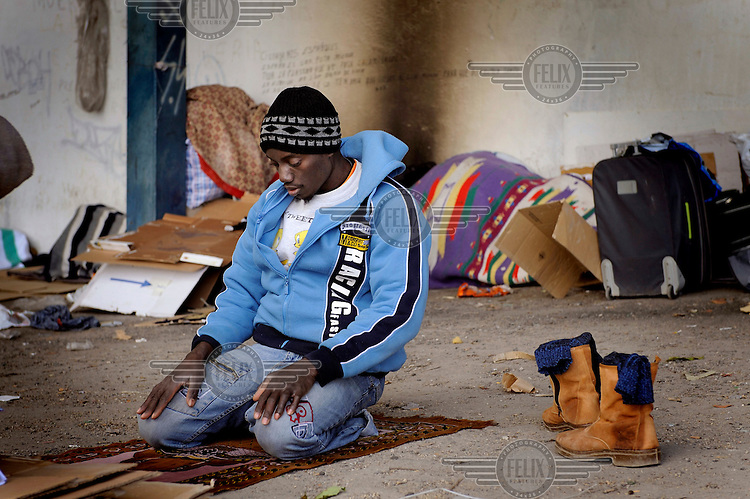 In an industrial park a Muslim migrant, from Sub-Saharan Africa, prays. Many of migrants come to the region to pick olives but this year there is competition for the work. The economic collapse means that work once shunned by the indigenous population is now sought after by unemployed Spaniards.