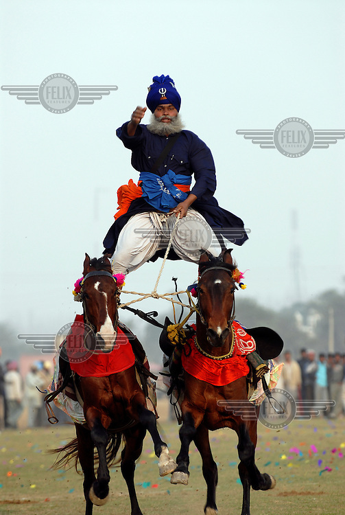 A Nihang Sikh warrior demonstrates his horse riding skills at the annual Kila Raipur Sports Festival (also known as the Rural Olympics).