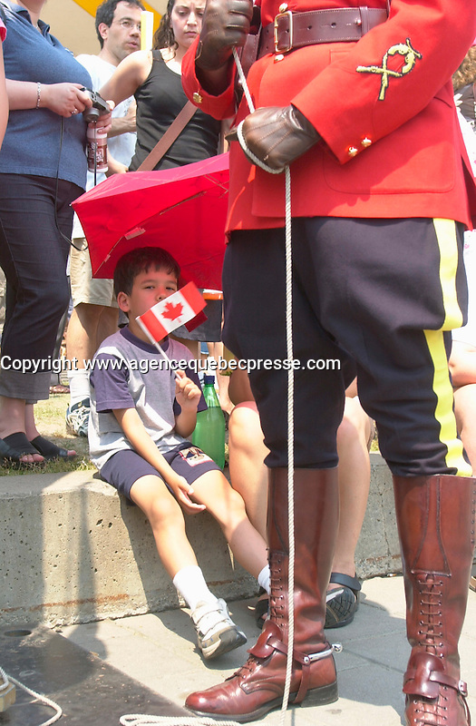 July 1 2002, Montreal, Quebec, Canada<br /> <br /> A young asian boy sit near an  RCMP officiers in Parade Uniform waiting to  raise the Canadian Flag,<br /> during the Canada day celebrations,  July 1st 2001, in the Old-Port of Montreal. <br /> <br /> Mandatory Credit: Photo by Pierre Roussel- Images Distribution. (&copy;) Copyright 2002 by Pierre Roussel <br /> <br /> NOTE l Nikon D-1 jpeg opened with Qimage icc profile, saved in Adobe 1998 RGB. Original file size available in TIFF file.