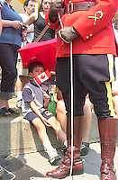 July 1 2002, Montreal, Quebec, Canada<br /> <br /> A young asian boy sit near an  RCMP officiers in Parade Uniform waiting to  raise the Canadian Flag,<br /> during the Canada day celebrations,  July 1st 2001, in the Old-Port of Montreal. <br /> <br /> Mandatory Credit: Photo by Pierre Roussel- Images Distribution. (©) Copyright 2002 by Pierre Roussel <br /> <br /> NOTE l Nikon D-1 jpeg opened with Qimage icc profile, saved in Adobe 1998 RGB. Original file size available in TIFF file.