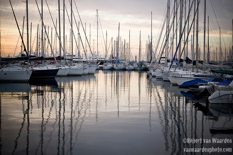 Sailing yachts reflected in the harbour in Cannes, France before the sunrise.