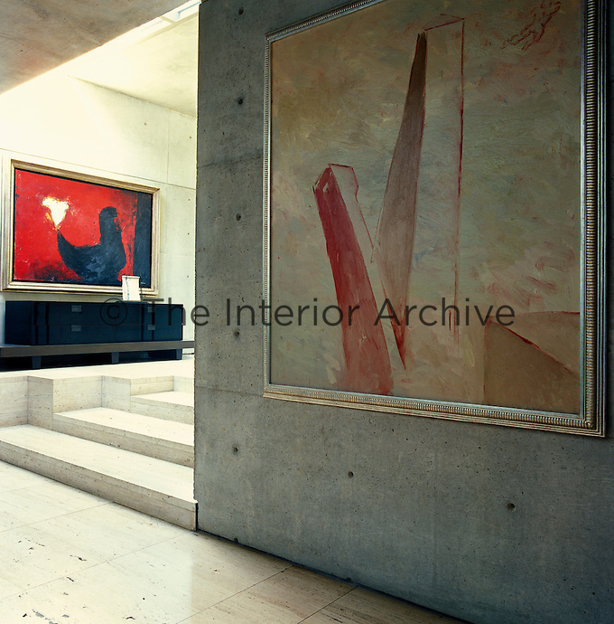The intrinsic beauty of the untreated concrete provides a neutral backdrop for a collection of modern art