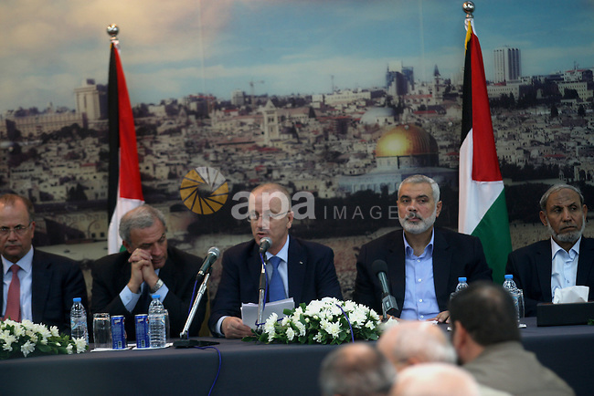 Palestinian Prime Minister Rami Hamdallah speaks to media during his visit to the senior Hamas leader Ismail Haniyeh, at Haniyeh's house in Gaza city on October 9, 2014. The Palestinian unity government which took the oath of office in June under technocrat prime minister Rami Hamdallah arrived to Gaza Strip on Thursday to convene the first fully meeting. Hamdallah said that the unity government will rebuild the bombed-out Gaza Strip following a seven-week Israeli offensive. Photo by Abed Rahim Khatib