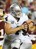 Oakland Raiders quarterback Derek Carr (4) looks for a receiver in fourth quarter action against the Washington Redskins at FedEx Field in Landover, Maryland on Sunday, September 24, 2017.  The Redskins won the game 27-10.<br /> Credit: Ron Sachs / CNP
