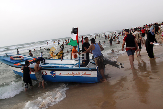 Palestinians enjoy the beach in Gaza City, Friday, June 11, 2010. Gaza has been mired in poverty for decades, but the embargo by Israel deepened the misery, erasing tens of thousands of jobs and preventing repair of damage from the Israeli offensive. Photo by Mohammed Asad