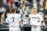 Michigan Wolverines third baseman Blake Nelson (10) greets teammate Jesse Franklin (7) at the plate against the Maryland Terrapins on April 13, 2018 in a Big Ten NCAA baseball game at Ray Fisher Stadium in Ann Arbor, Michigan. Michigan defeated Maryland 10-4. (Andrew Woolley/Four Seam Images)