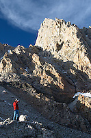 Man sitting on boulder drinking from water bottle below the Grand Teton, Lower Saddle, Grand Teton National Park, Teton County, Wyoming, USA