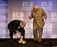 Adidas' Antonio Zea presents Archbishop Desmond Tutu with a pair of personalized soccer cleats during the US Soccer Foundation Gala held at City Center in Washington, DC.