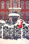 West Fourth Street victorian house in winter with ornate fence, red ribbon, and snow.