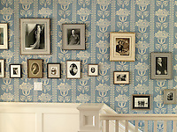 A collection of vintage family photographs is displayed up the staircase and along the first floor landing against traditional blue and white striped wallpaper with a bouquet motif