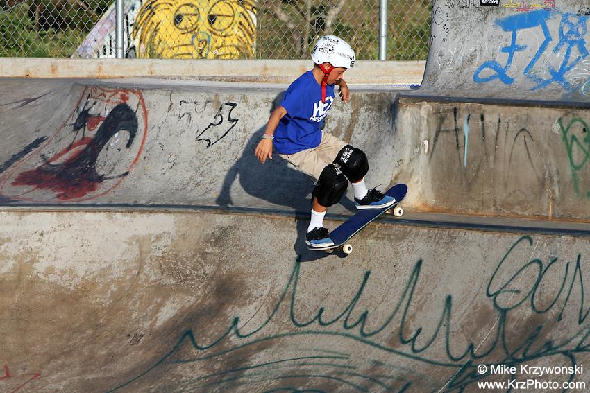 Young boy skateboarding at the Banzai Skate Park, North Shore, Oahu, Hawaii