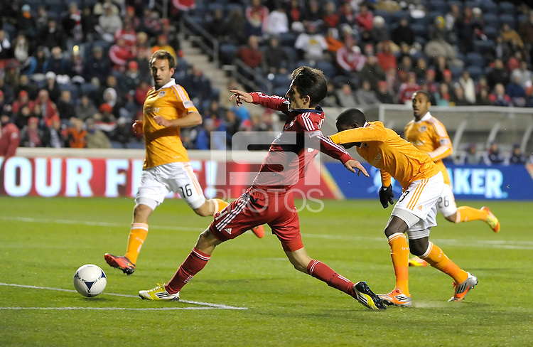 Chicago midfielder Alvaro Fernandez (4) shoots the ball in front of Houston defender Kofi Sarkodie (8).  The Houston Dynamo defeated the Chicago Fire 2-1 in the Eastern Conference play-in game for the MLS Playoffs at Toyota Park in Bridgeview, IL on October 31, 2012.