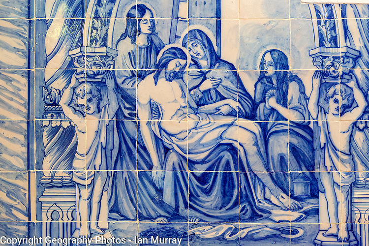 Blue and white traditional Azulejo ceramic tiles forming picture of the dead body of Jesus Christ being cared for by the three Marys, Evora, Alto Alentejo, Portugal, southern Europe