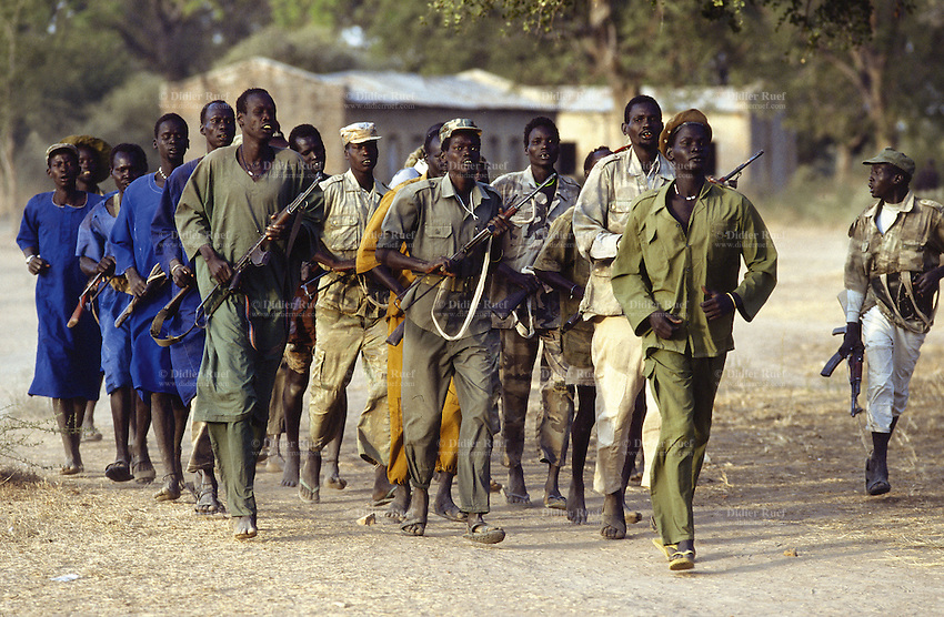 Sudan. South Sudan. Bahr El Ghazal. Mayen Abun. SPLA ( Sudanese People Liberation Army) dinka soldiers jogging and holding machine guns in hands in the early morning. They pass by a catholic church. © 1999 Didier Ruef