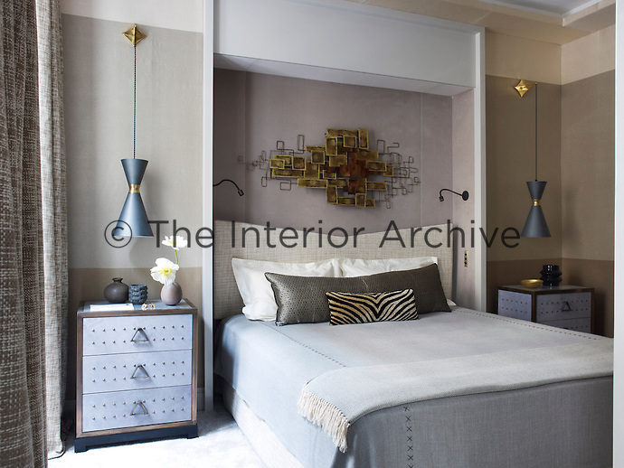 The master bedroom's wall covering is by Le Manache, and Stilnovo light fixtures are suspended above bedside tables Deniot designed for Colllection Pierre; the alcove is covered in a velvet by Zimmer and Rohde, and the C. Jere wall sculpture was purchased at auction