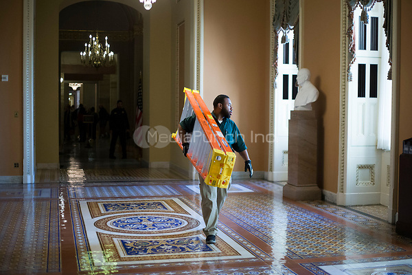A member of the Architect of the United States Capitol staff carries a ladder near the US Senate Chamber in the US Capitol in Washington, DC on Friday, December 1, 2017. Credit: Alex Edelman / CNP /MediaPunch