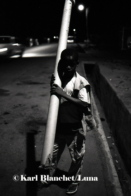 A young boy carrying a piece of steel during the night. Wa, Ghana.