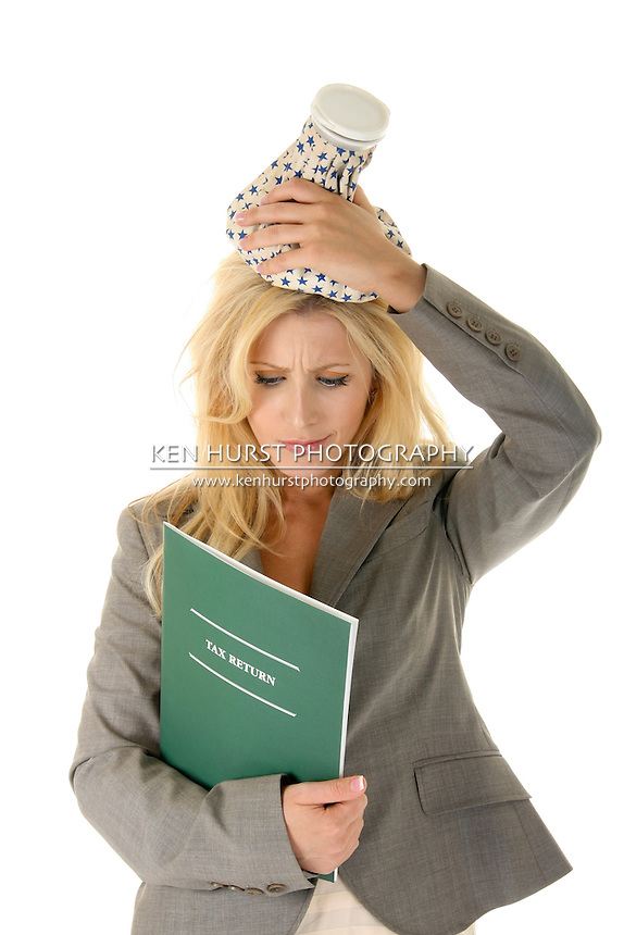 "Beautiful blonde woman is treating her tax headache with an ice pack on her head. Other text could be substituted for the ""tax return"" text."