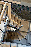 An overhead view of the staircase reveals grey-painted steps covered with a stair carpet of natural matting and a wooden handrail