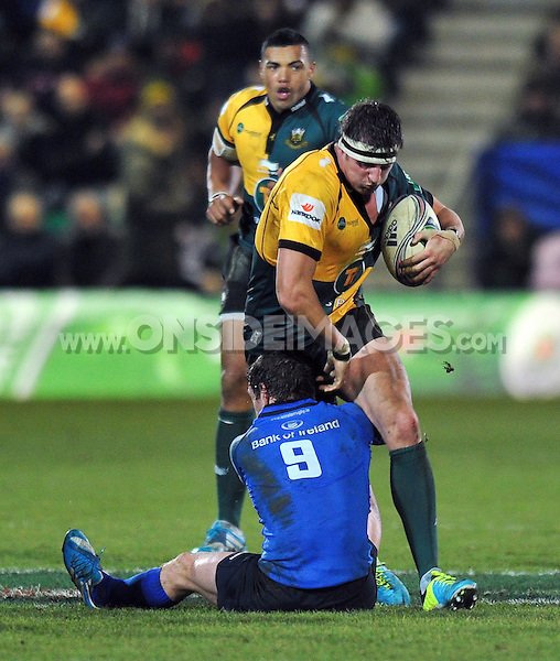 Tom Wood is tackled by Eoin Reddan. Heineken Cup match, between Northampton Saints and Leinster on December 7, 2013 at Franklin's Gardens in Northampton, England. Photo by: Patrick Khachfe / JMP