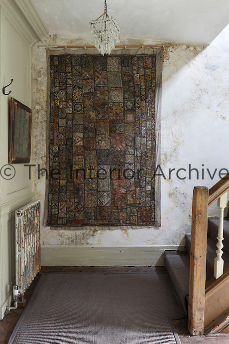 An embroidered patchwork quilt is hung from a pole as a wall hanging in a hallway. The wall and radiator are given a distressed finish.