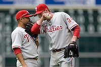 Philadelphia Phillies 3B Placido Polanco and pitcher Roy Halladay discuss strategy against the Houston Astros on Sunday April 11th, 2010 at Minute Maid Park in Houston, Texas.  (Photo by Andrew Woolley / Four Seam Images)