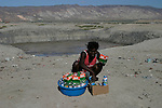 February 17, 2004. Gonaive, Haiti. A lady sells food stuff in front of the salt mines in Gonaive.