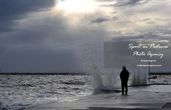 The sea splahes as a boy watches on. Stormy seas. Southend sea front. Essex. 04/01/2014. MANDATORY Credit Garry Bowden/Sportinpictures - NO UNAUTHORISED USE - 07837 394578