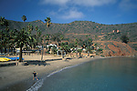 Child throwing rocks into water on sand beach, Two Harbors, Catalina Island, California