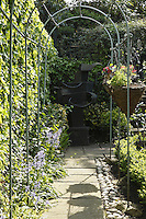 A metal pergola lines the paved pathway in a corner of the garden in which is displayed a contemporary sculpture