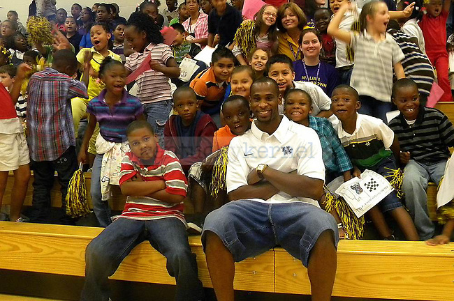 UK's two time basketball national champion Wayne Turner poses with Wells Brown Elementary students  after an academic pep rally, Friday, September 24, 2010.Turner has returned to UK to complete his degree and will graduate in May.  Photo by Theresa   Staff
