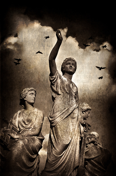 Three female statues with stormy clouds and birds in Brompton Cemetery, London