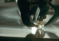 A rough diamond being cut and shaped.