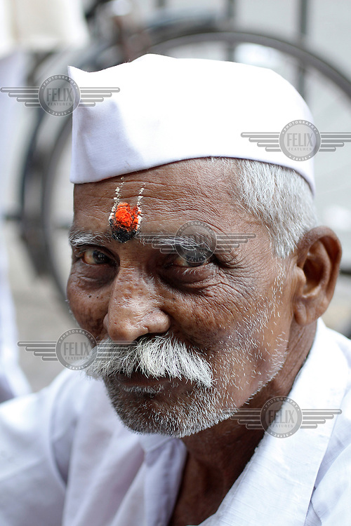 "Portrait of a dabbawala distributing food in Mumbai . A dabbawala.(literally meaning ""person with a box""), is a person, most commonly found in the city of Mumbai, who is employed in a service industry whose primary business is collecting the freshly cooked food in lunch boxes from the residences of the office workers, delivering it to their respective workplaces and returning the empty boxes back to the customer's residence by using various modes of transport."