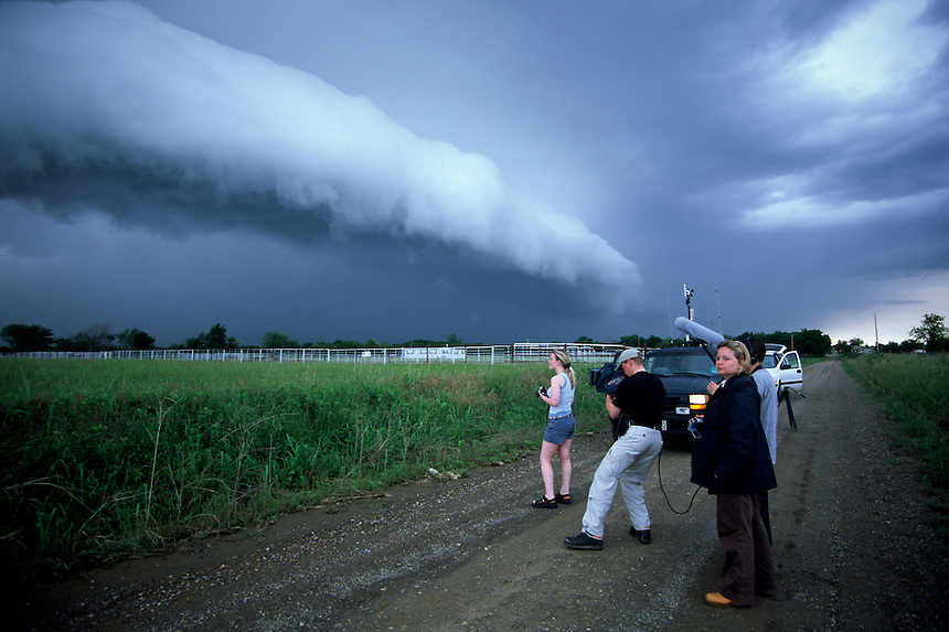 Television crews interviewing a storm chaser while a thunderstorm approaches.