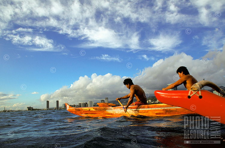 Koa canoe in the water off of Oahu with beautiful blue skies in the background