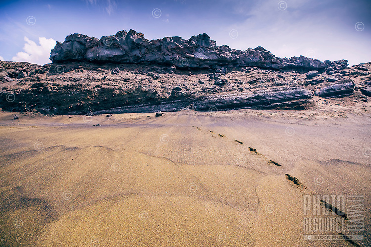 Footprints lead from rugged geological formations to the shore of a remote beach in Ocean View, Hawai'i Island.