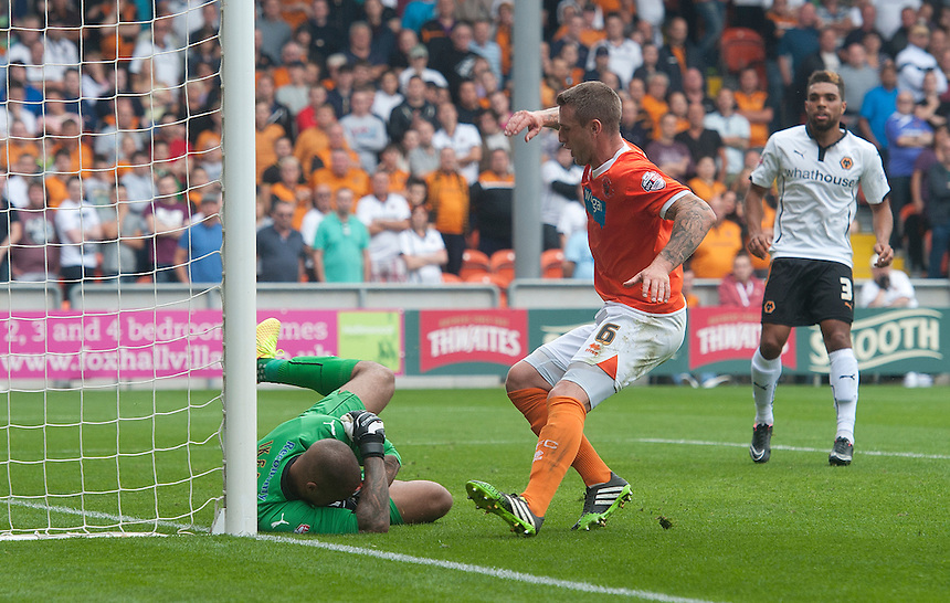 Wolverhampton Wanderers' Carl Ikeme saves at the feet of Blackpool's Peter Clarke<br /> <br /> Photographer Stephen White/CameraSport<br /> <br /> Football - The Football League Sky Bet Championship - Blackpool v Wolverhampton Wanderers - Saturday 13th September 2014 - Bloomfield Road - Blackpool<br /> <br /> &copy; CameraSport - 43 Linden Ave. Countesthorpe. Leicester. England. LE8 5PG - Tel: +44 (0) 116 277 4147 - admin@camerasport.com - www.camerasport.com