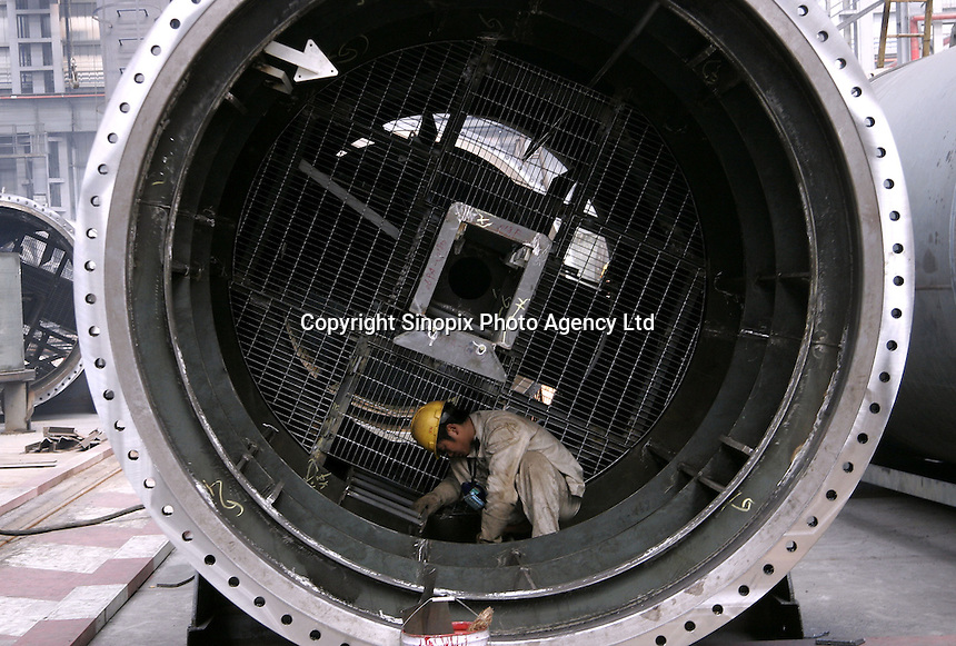 A Chinese worker paints the interior of a large duct at the Hudong Zhonghua Shipbuilding Co., LTD in Shanghai, China. China is the world's third largest shipbuilding nation after South Korea and Japan. While growing international interest in its lower building cost and domestic tanker demand to fulfill the country's hunger for energy is likely to push the country to the top position, the rapidly increasing price of steel has also undercut the industry's profitability..