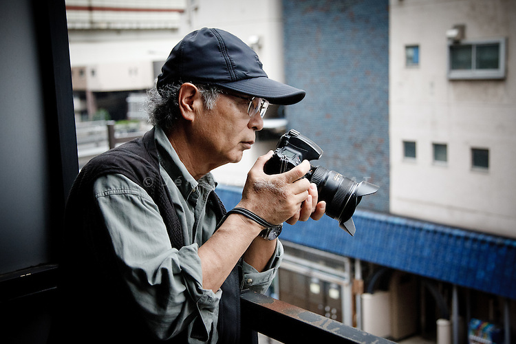 "Tokyo, June 10 2011 - The Japanese photographer Ryuichi Hirokawa taking some pictures of the passer-bies near ""Days japan"" magazine's office. M. Hirokawa is also editor in chief of the magazine."
