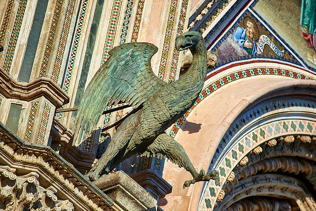 Bronze statue of an eagle  representing the the Evangelist John created by Maitani and collaborators between 1325 and 1330 on the14th century Tuscan Gothic style facade of the Cathedral of Orvieto, designed by Maitani, Umbria, Italy