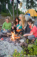 A group of girlfriends cooking a meal outdoors on the campfire.