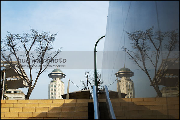 The Radisson Hotel building reflected on the shiny marble wall of an under pass in Shanghai, China.