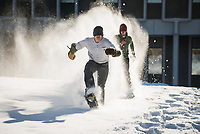 Leaders in the blindfolded snowshoe race make their way to the finish line on UAA's Cuddy Quad during Winterfest festivities.