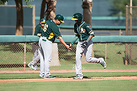Oakland Athletics shortstop Jhoan Paulino (17) is congratulated by the third base coach after hitting a home run during an Instructional League game against the Los Angeles Dodgers at Camelback Ranch on October 4, 2018 in Glendale, Arizona. (Zachary Lucy/Four Seam Images)