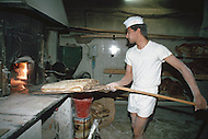 "April 27, 1990, Rome, Italy. Photographing for the book ""One day in the life of Italy"", this is an exploration of Rome. In Trastevere at 4am, Fabio Arnese is making traditional large loaves of bread."
