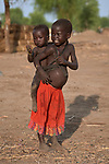 A girl carries her younger sibling on her back in the Doro Refugee Camp in Maban County, South Sudan. Doro is one of four camps in Maban that together shelter more than 130,000 refugees from the Blue Nile region of Sudan. Jesuit Refugee Service provides educational and psycho-social services to both refugees and the host community. <br /> <br /> Misean Cara supports the work of JRS in the Maban camps.