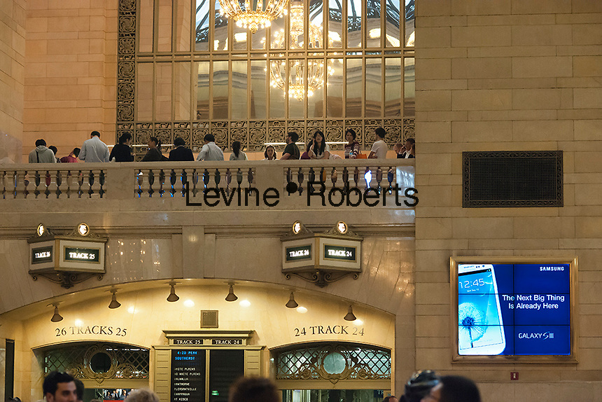 Above an advertisement for the Samsung Galaxy S III, customers on line in the Apple store in Grand Central Terminal to purchase an iPhone 5 on Friday, September 21, 2012.  The fifth generation of Apple's iPhone, the iPhone 5,  went on sale today bringing crowds and lines to Apple stores around the world. (© Richard B. Levine)