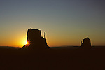 Sunrise over Monument Valley with the two Mittens silhouetted with the sun peaking around one, Arizona State USA